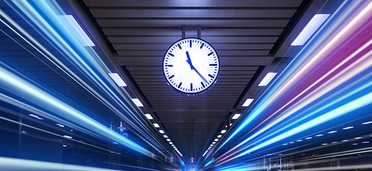 Clock in train station showing long exposure blurred trains, to indicate speed